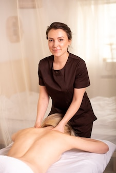 Massage du dos et des épaules par un kinésithérapeute souriant