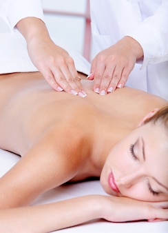 Massage du dos pour la jolie jeune femme