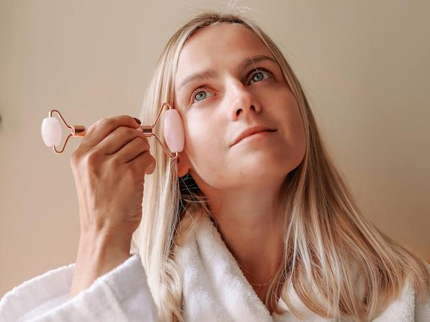 Massage du visage. une belle jeune femme blonde fait un massage du visage à l'aide d'un rouleau de jade.