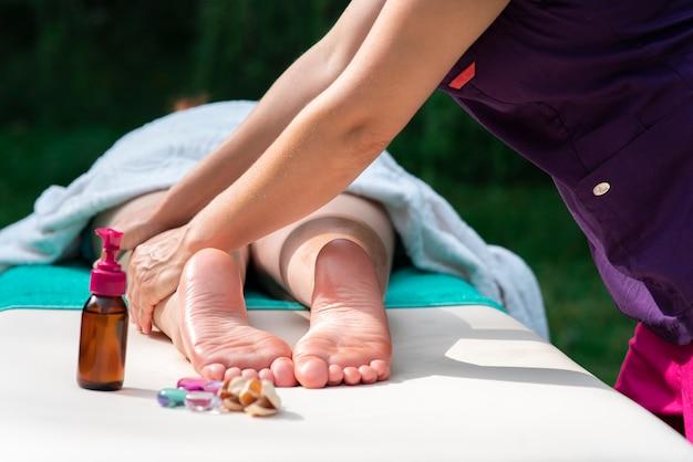 Massage des jambes pieds féminins avec des pierres d'huile à l'extérieur photo en gros plan du pied de la femme et des thérapeutes