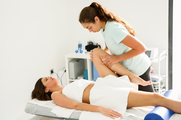 Massage médical à la jambe dans un centre de physiothérapie.