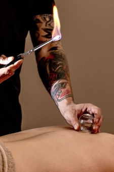 Massage par ventouses. jeune homme appréciant le massage du dos et des shouders dans le spa. massothérapeute professionnel traite un patient de sexe masculin. concept de traitement de relaxation, beauté, corps et visage.