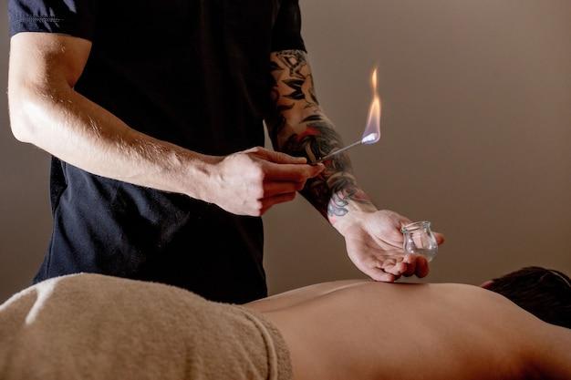 Massage par ventouses jeune homme bénéficiant d'un massage du dos et des épaules au spa