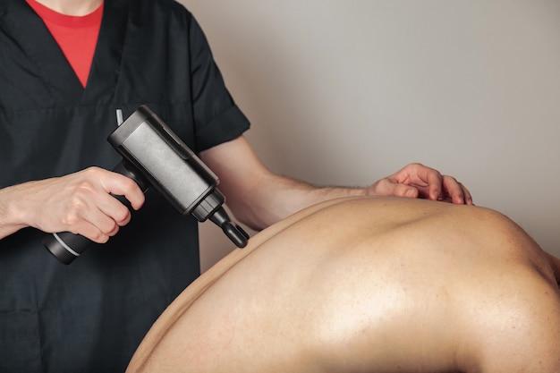 Massage de percussion de pistolet de sport dans la salle médicale du gymnase. masseur fait des exercices de massage à domicile