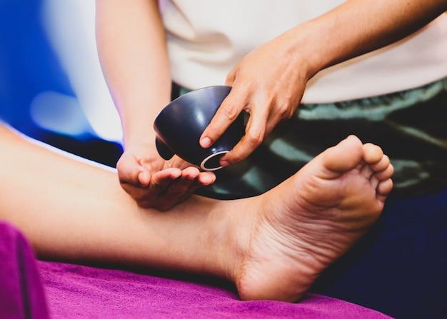 Massage des pieds et des jambes, thérapeute versant de l'huile sur un pied sur le point de masser