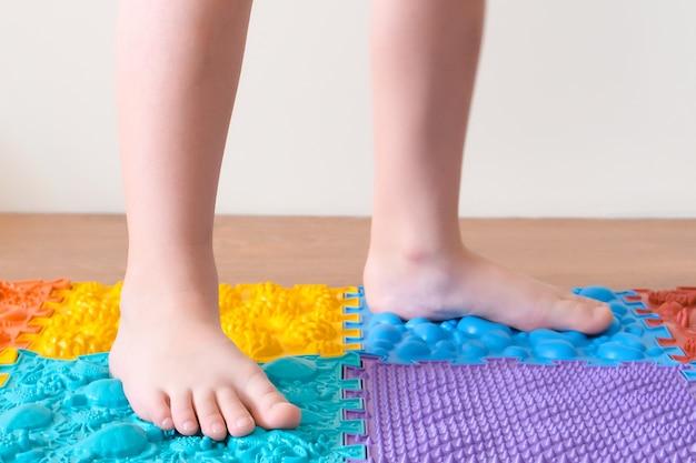 Massage des pieds. les pieds des enfants marchent sur des tapis orthopédiques. traitement et prévention des pieds plats et des maladies des jambes