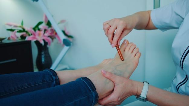 Massage des pieds shiatsu à l'aide d'une baguette au salon de beauté. concept de soins de santé. photo en gros plan.