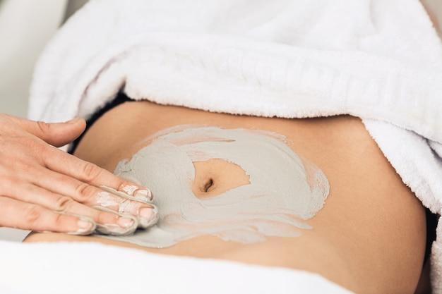 Massage professionnel de l'abdomen à l'argile.