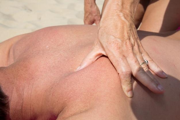 Massage relaxant sur le sable de la plage de l'hôtel pendant les vacances d'été