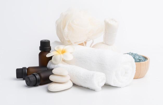 Massage spa, fleurs de frangipanier tropical exotique, sérum, gommage aux herbes, pierres zen, serviettes blanches et cristal de sel bleu sur blanc