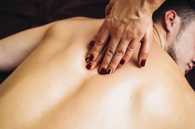 Massage tantrique relaxant pour homme à quatre mains utilisant des huiles d'aromathérapie