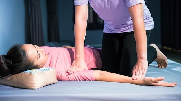 Massage thaï des bras sur le lit dans le salon spa. portrait d'une belle femme asiatique massant et relaxant.