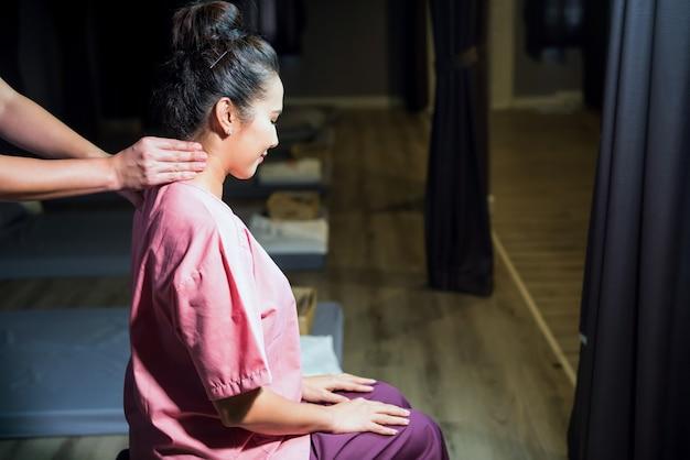 Massage thaï du cou dans un salon spa. portrait d'une femme souriante asiatique massant et se relaxant sur une chaise.