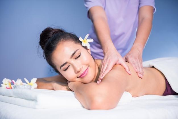 Massage thaï à l'huile de jeune femme asiatique belle avec plumeria blanc dans le spa