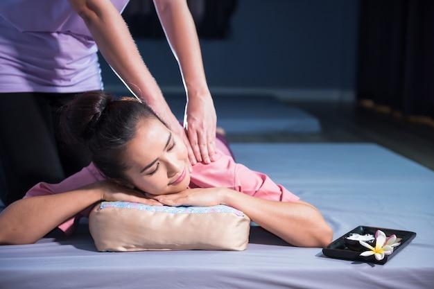Massage thaïlandais à une femme asiatique en spa