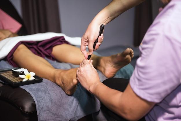 Massage thaïlandais des pieds avec un bâton en bois