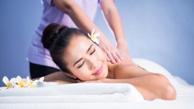 Massage thaïlandais en spirale du dos et des épaules à une jeune belle femme asiatique