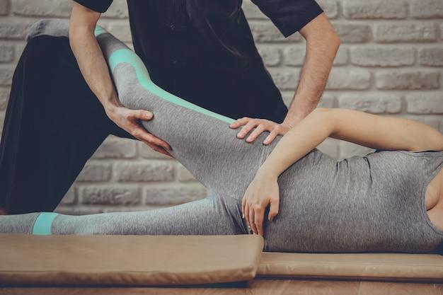 Massage thaïlandais traditionnel de femme enceinte allongée sur le tapis dans un studio de yoga. un jeune masseur blanc vêtu d'un uniforme noir étire sa jambe avec ses mains. mur de briques en arrière-plan. notion de santé