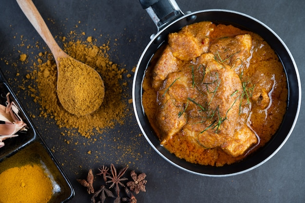 Massaman au curry dans une poêle avec des épices sur le sol en ciment