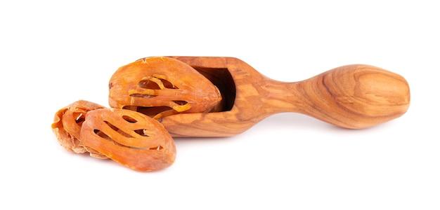 Masse dans une cuillère en bois, isolé sur fond blanc. fleur de noix de muscade, myristica fragrans. épice naturelle, assaisonnement asiatique.