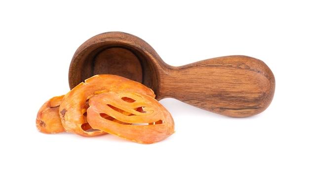 Masse dans une cuillère en bois, isolée sur fond blanc. fleur de noix de muscade, myristica fragrans. épice naturelle, assaisonnement asiatique.