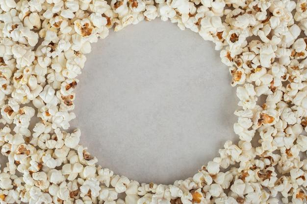 Masse de pop-corn avec un espace circulaire vide au milieu, sur marbre.