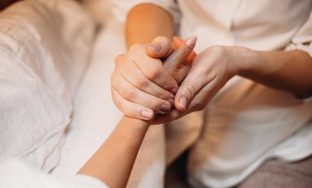 Un masseur caucasien masse la main du client et la prépare pour la prochaine procédure de spa