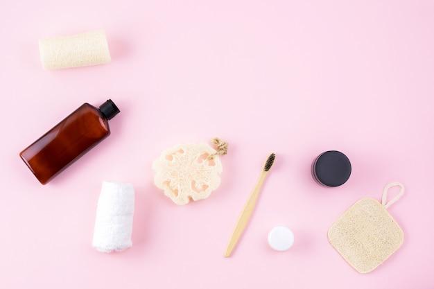 Masseur, crème, bouteille, éponge à récurer luffa éponge, brosse à dents en bambou sur surface rose