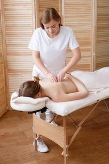 Masseur délègue un massage thérapeutique au patient
