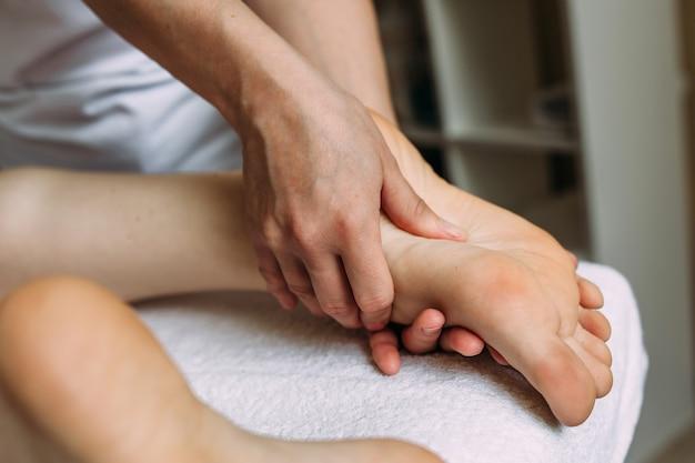 Le masseur donne un massage aux pieds féminins au spa
