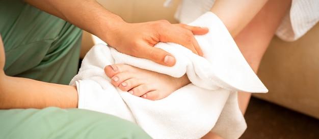 Masseur essuyant les jambes de la femme après un massage des pieds dans le salon spa