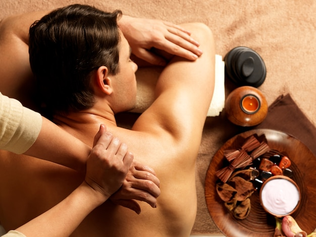 Masseur faisant le massage de la colonne vertébrale sur le corps de l'homme dans le salon spa. concept de traitement de beauté.