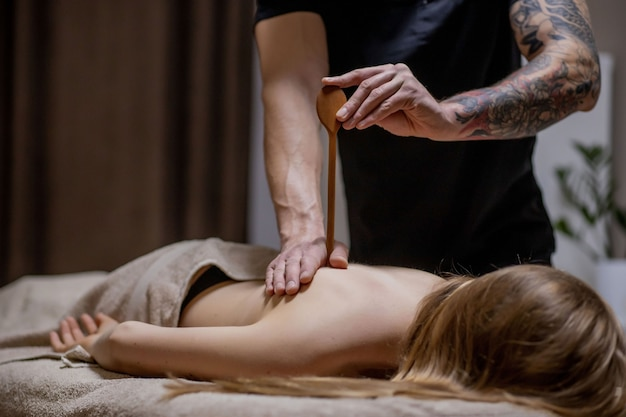Masseur faisant un massage sur le corps de l'homme dans le salon spa. concept de traitement de beauté.