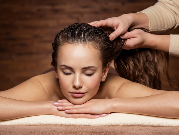Masseur faisant masser la tête et les cheveux pour une femme dans un salon spa