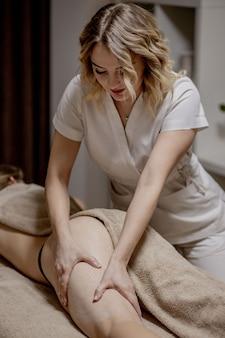 Masseur fait massage anticellulite jeune femme dans un salon de spa