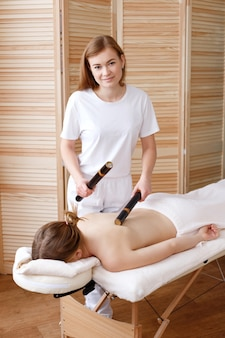 Masseur fait un massage avec des bâtons de bambou