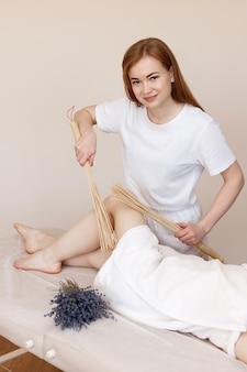 Masseur fait un massage des pieds avec des baguettes