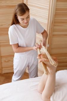 Masseur fait un massage des pieds dans le salon