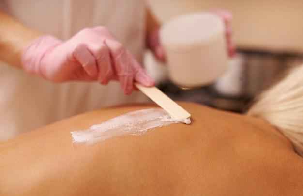 Masseur féminin applique un gommage à la crème de massage à l'aide d'une spatule en bois sur le dos d'une jeune femme allongée sur une table de massage et bénéficiant d'une séance de thérapie au salon spa