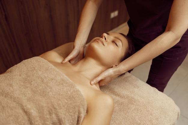 Masseur féminin dorlotant le cou d'une jeune femme mince en serviette, massage professionnel. massages et relaxation, soins du corps et de la peau. dame attirante dans le salon de station thermale