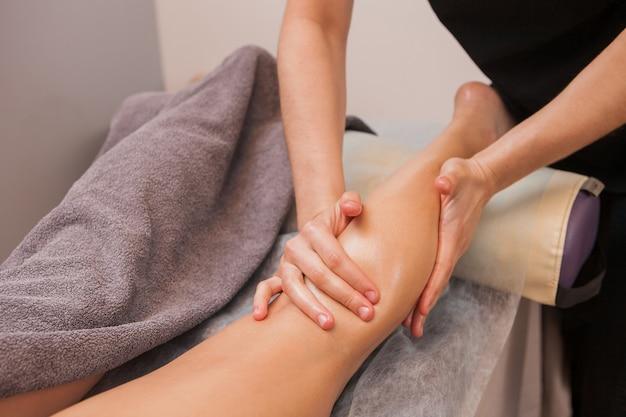 Un masseur féminin prépare un massage anticellulite à une jambe de jeune femme
