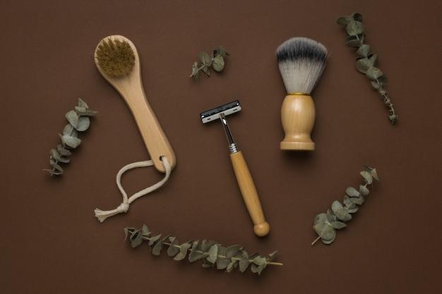 Masseur à main et accessoires de rasage avec branches d'eucalyptus sur fond marron. mise à plat.