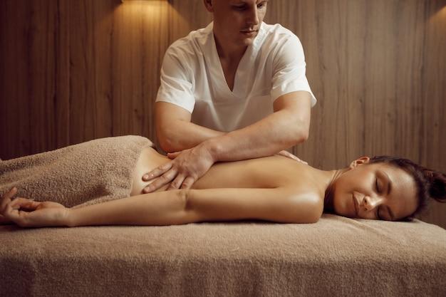 Masseur masculin dorlotant le cou d'une jeune femme en serviette, massage professionnel. massages et relaxation, soins du corps et de la peau. dame attirante dans le salon de station thermale