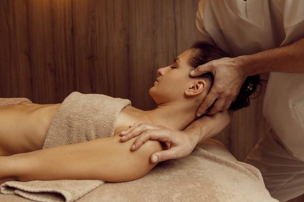 Masseur masculin frottant les vertèbres du cou à une jeune femme en serviette, massage professionnel. massages et relaxation, soins du corps et de la peau. dame attirante dans le salon de station thermale