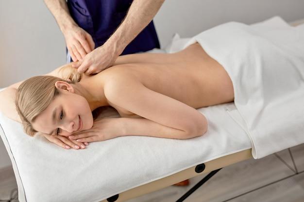 Masseur masculin massant le dos et les omoplates d'une femme allongée sur un canapé de massage au spa