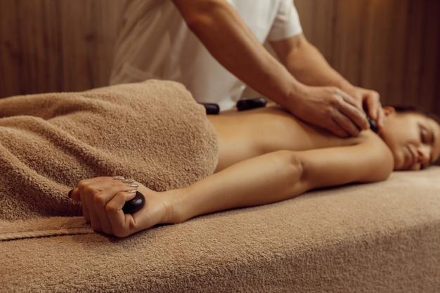 Un masseur masculin met des pierres sur le dos d'une femme mince en serviette, massage professionnel. massages et relaxation, soins du corps et de la peau. dame attirante dans le salon de station thermale