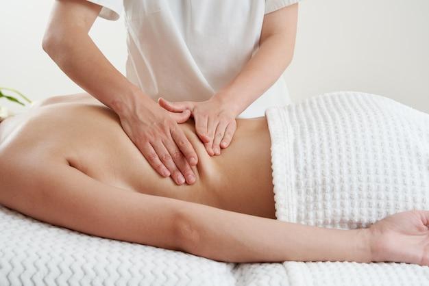 Masseur de massage du dos massant une jeune femme sur une table de massage dans un salon de spa jeune femme relaxante pendant