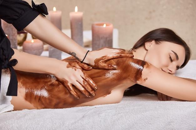Masseur massant le dos de la femme avec un masque de cacao dans un salon de spa