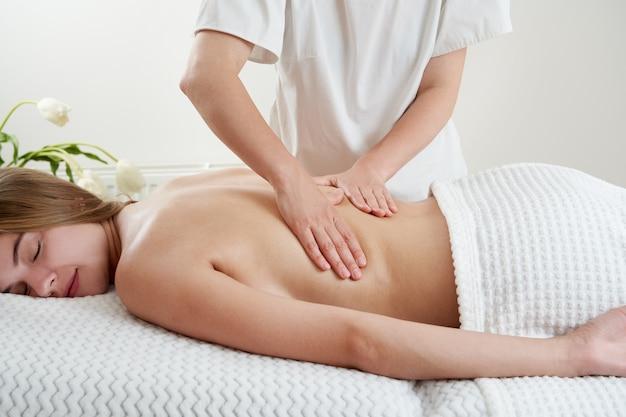 Masseur massant une jeune femme sur une table de massage dans un salon de spa jeune femme se relaxant pendant un massage du dos
