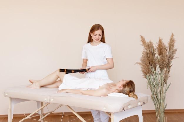 Un masseur masse une femme avec des bâtons de bambou